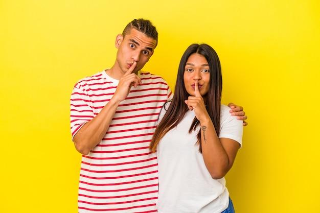 Jeune couple latin isolé sur fond jaune gardant un secret ou demandant le silence.