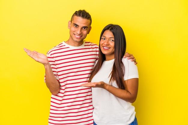 Jeune couple latin isolé sur fond jaune montrant un espace de copie sur une paume et tenant une autre main sur la taille.