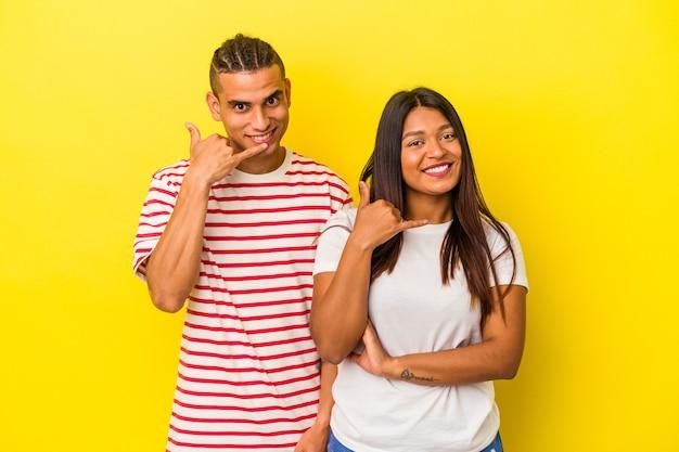 Jeune couple latin isolé sur fond jaune montrant un geste d'appel de téléphone portable avec les doigts.