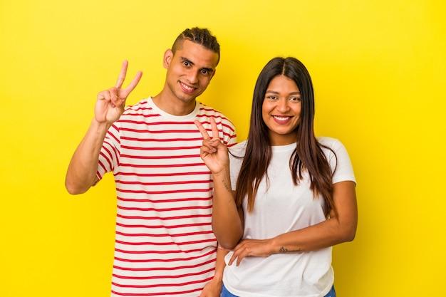Jeune couple latin isolé sur fond jaune montrant le numéro deux avec les doigts.