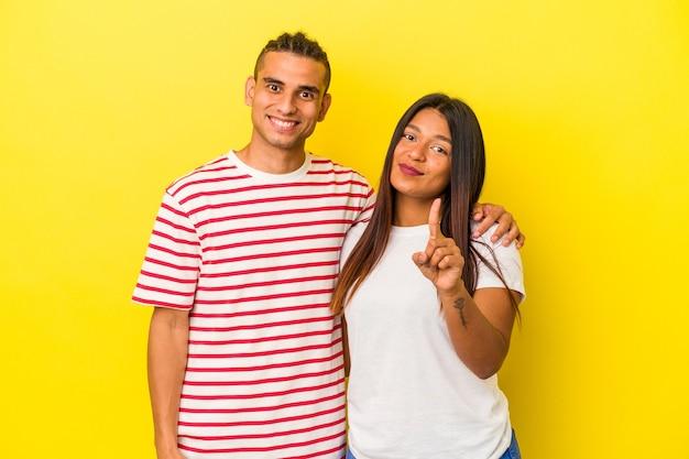 Jeune couple latin isolé sur fond jaune montrant le numéro un avec le doigt.