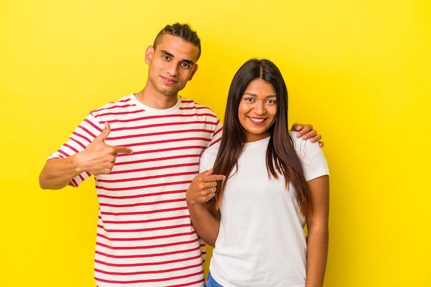 Jeune couple latin isolé sur fond jaune personne pointant à la main vers un espace de copie de chemise, fier et confiant