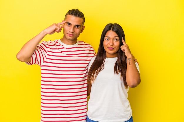 Jeune couple latin isolé sur fond jaune pointant le temple avec le doigt, pensant, concentré sur une tâche.