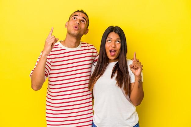 Jeune couple latin isolé sur fond jaune pointant vers le haut avec la bouche ouverte.