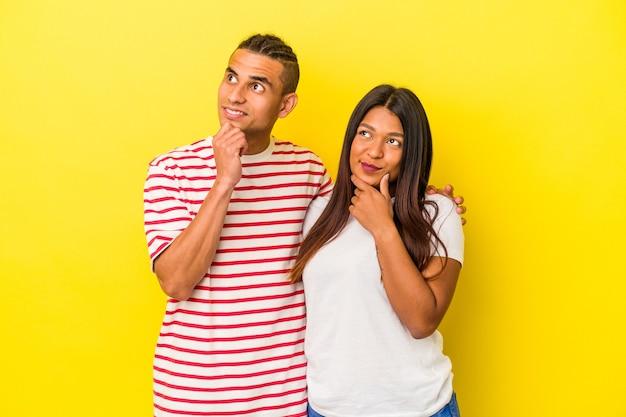 Jeune couple latin isolé sur fond jaune regardant de côté avec une expression douteuse et sceptique.