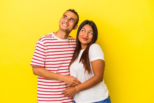 Jeune couple latin isolé sur fond jaune rêvant d'atteindre des objectifs et des buts