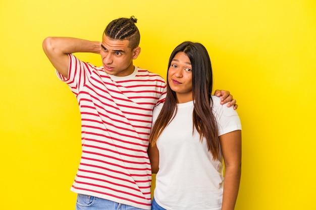Jeune couple latin isolé sur fond jaune touchant l'arrière de la tête, pensant et faisant un choix.
