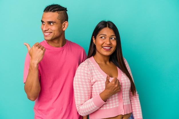 Jeune couple latin isolé sur des points de mur bleus avec le pouce loin, riant et insouciant.