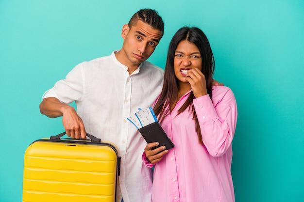 Jeune couple latin partant en voyage isolé sur fond bleu se rongeant les ongles, nerveux et très anxieux.