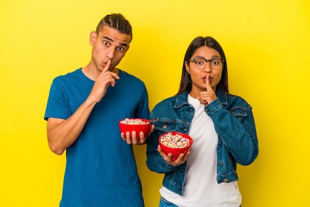 Jeune couple latin tenant un bol de céréales isolé sur fond jaune gardant un secret ou demandant le silence.