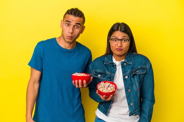 Jeune couple latin tenant un bol de céréales isolé sur fond jaune hausse les épaules et ouvre les yeux confus.