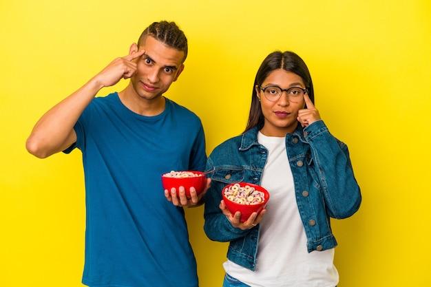 Jeune couple latin tenant un bol de céréales isolé sur fond jaune pointant le temple avec le doigt, pensant, concentré sur une tâche.