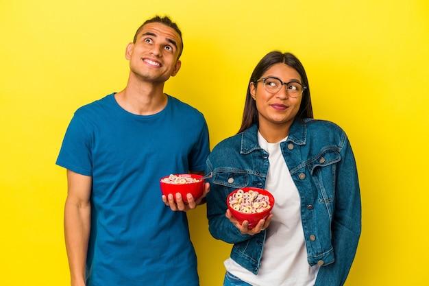 Jeune couple latin tenant un bol de céréales isolé sur fond jaune rêvant d'atteindre des objectifs et des objectifs