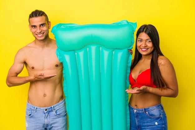 Jeune couple latin tenant un matelas pneumatique isolé sur fond jaune montrant un espace de copie sur une paume et tenant une autre main sur la taille.