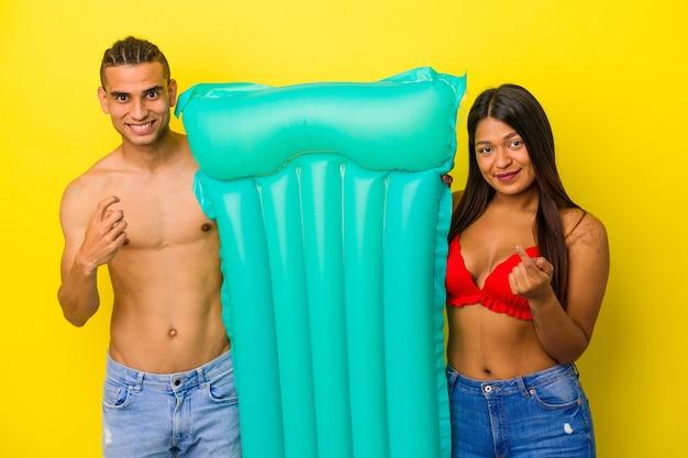Jeune couple latin tenant un matelas pneumatique isolé sur fond jaune pointant le doigt vers vous comme s'il vous invitait à vous rapprocher.