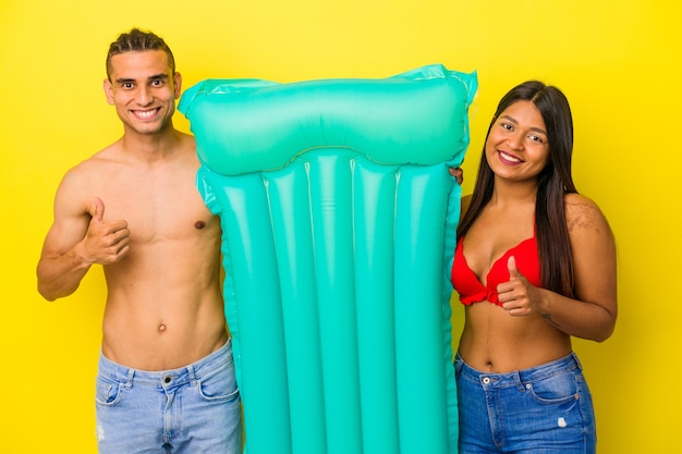 Jeune Couple Latin Tenant Un Matelas Pneumatique Isolé Sur Fond Jaune Souriant Et Levant Le Pouce Vers Le Haut Photo Premium