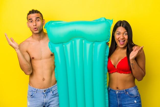 Jeune couple latin tenant un matelas pneumatique isolé sur fond jaune surpris et choqué.