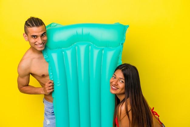 Jeune couple latin tenant un matelas pneumatique isolé sur fond jaune