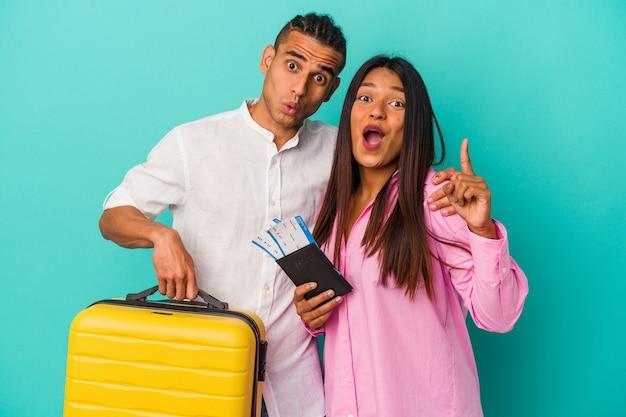 Jeune couple latin va voyager isolé sur fond bleu ayant une idée, concept d'inspiration.