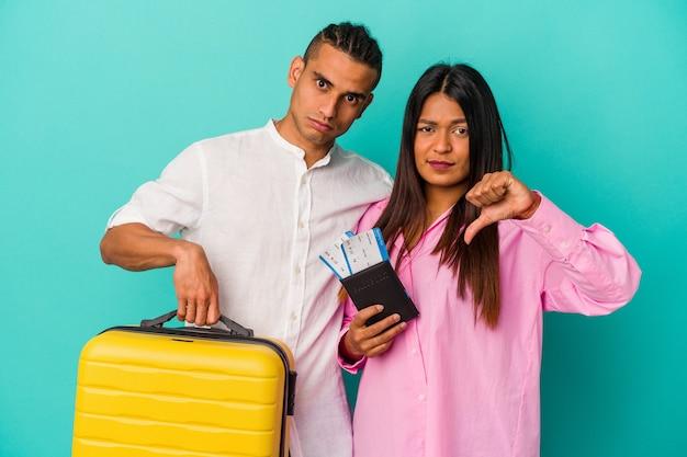 Jeune couple latin va voyager isolé sur fond bleu montrant un geste d'aversion, les pouces vers le bas. notion de désaccord.