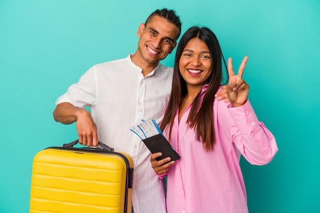Jeune couple latin va voyager isolé sur fond bleu montrant le numéro deux avec les doigts.