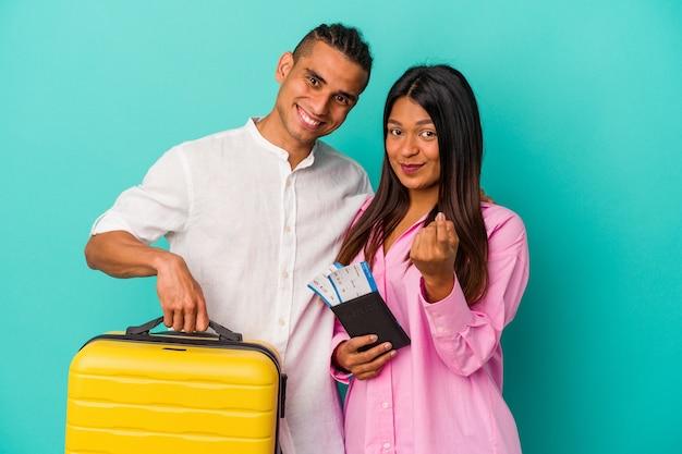 Jeune couple latin va voyager isolé sur fond bleu pointant du doigt vers vous comme s'il vous invitait à vous rapprocher.