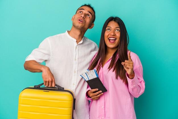 Jeune couple latin va voyager isolé sur un mur bleu pointant vers le haut avec la bouche ouverte.
