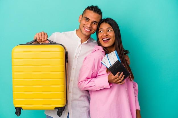 Jeune couple latin va voyager isolé sur mur bleu