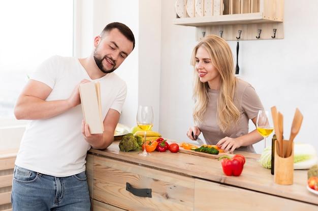 Jeune couple, lecture livre, cuisine