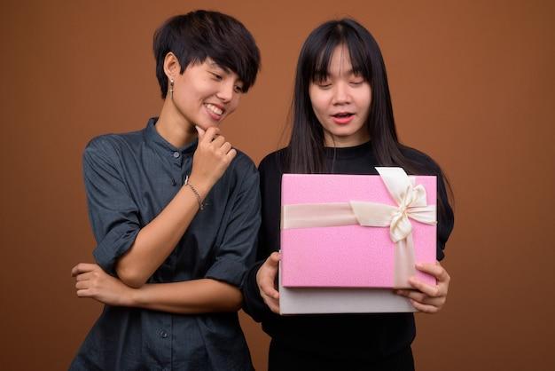 Jeune couple de lesbiennes asiatiques ensemble et amoureux contre brun