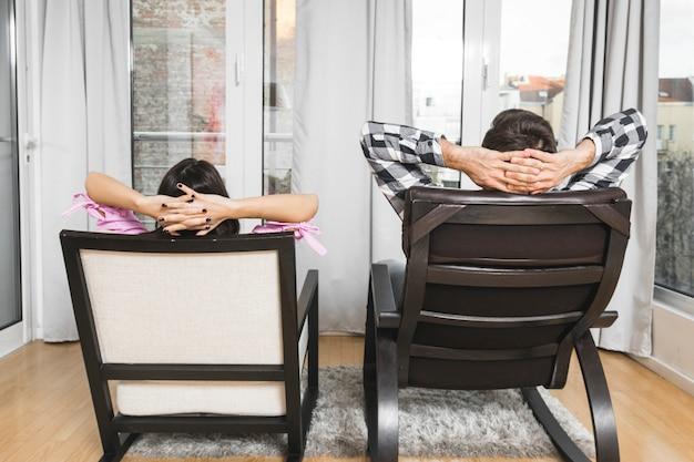 Jeune couple avec leurs mains derrière la tête, assis sur une chaise à la maison