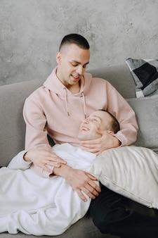 Jeune couple lgbtq romantique passant la journée à se câliner et à se détendre sur le canapé. concept de mode de vie familial différent.