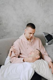 Jeune couple lgbtq romantique passant la journée à se câliner et à se détendre sur le canapé