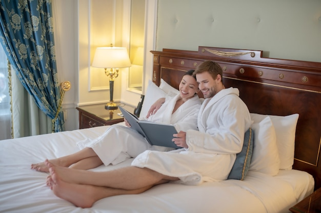 Un jeune couple lisant un livre ensemble dans leur chambre