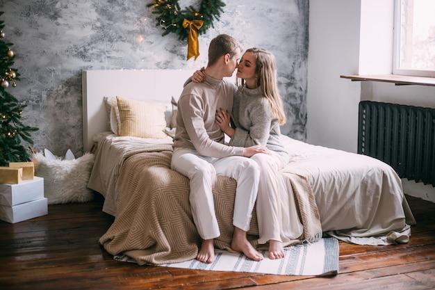 Jeune couple sur lit à la maison au moment de noël