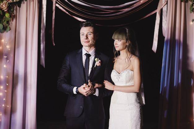 Jeune couple lors de la cérémonie de mariage de nuit. arc de mariage avec ampoule à l'extérieur.