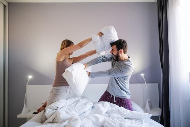 Jeune couple ludique ayant une bataille d'oreillers le matin dans la chambre.
