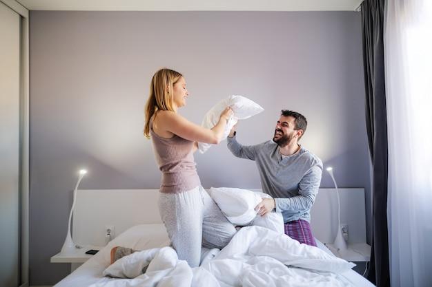 Jeune couple ludique ayant une bataille d'oreillers le matin dans la chambre