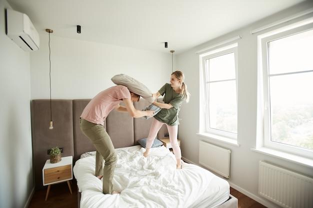 Jeune couple ludique se battre avec des oreillers