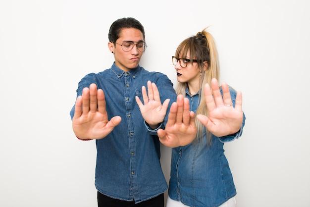 Jeune couple avec des lunettes faisant arrêt geste pour déçu