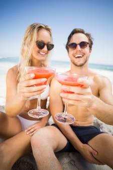 Jeune couple à lunettes de soleil montrant un verre à cocktail sur la plage