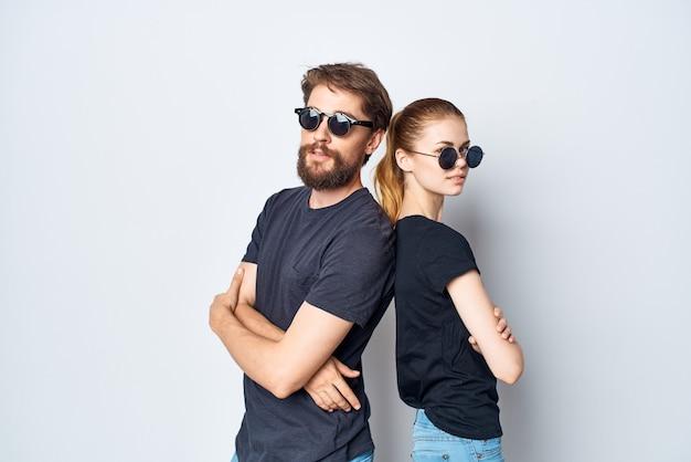 Un jeune couple en lunettes de soleil tshirt noir posant sur fond clair