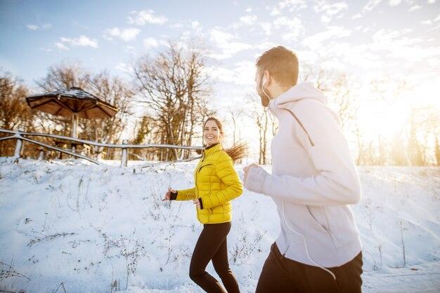 Jeune couple magnifique, passer du temps dans la nature à courir et à écouter de la musique.