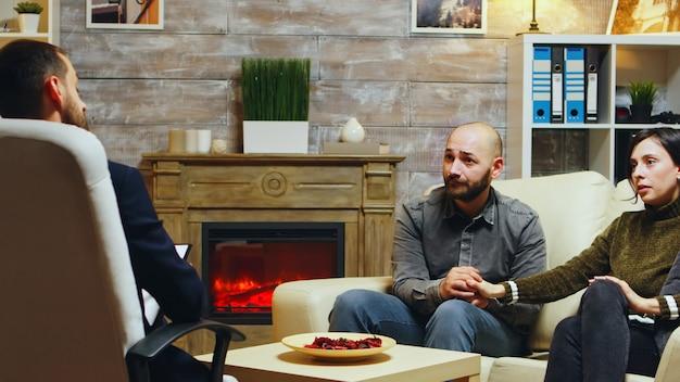 Jeune couple main dans la main assis sur le canapé à la thérapie de couple. petite amie en colère.