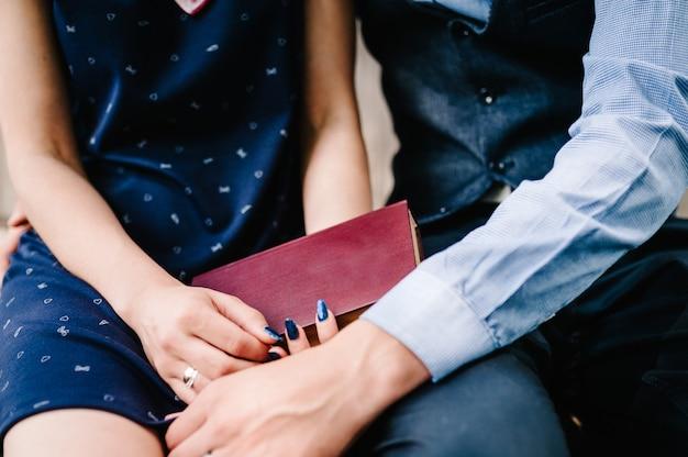 Un jeune couple mains tient un livre fermé sur les genoux