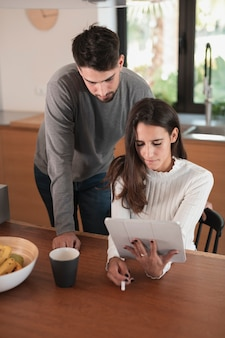 Jeune couple à la maison à l'aide d'une tablette