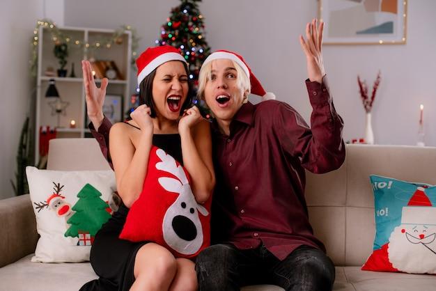 Jeune couple à la maison au moment de noël portant bonnet de noel assis sur un canapé dans le salon