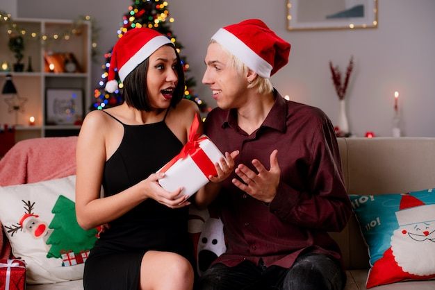 Jeune couple à la maison à l'époque de noël portant bonnet de noel assis sur un canapé dans le salon à se regarder impressionné