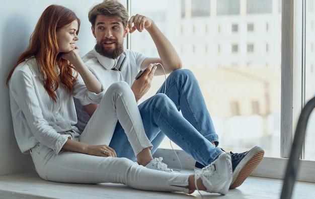 Jeune couple à la maison près de la fenêtre technologie communication