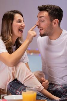 Jeune couple, manger, bonbons, dans lit